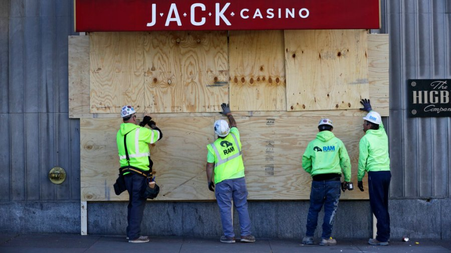Workers install plywood over broken windows at Jack Casino in Cleveland. The City of Cleveland extended its curfew through Tuesday night after riots broke out on Saturday over the death of George Lloyd. (AP Photo/Tony Dejak)