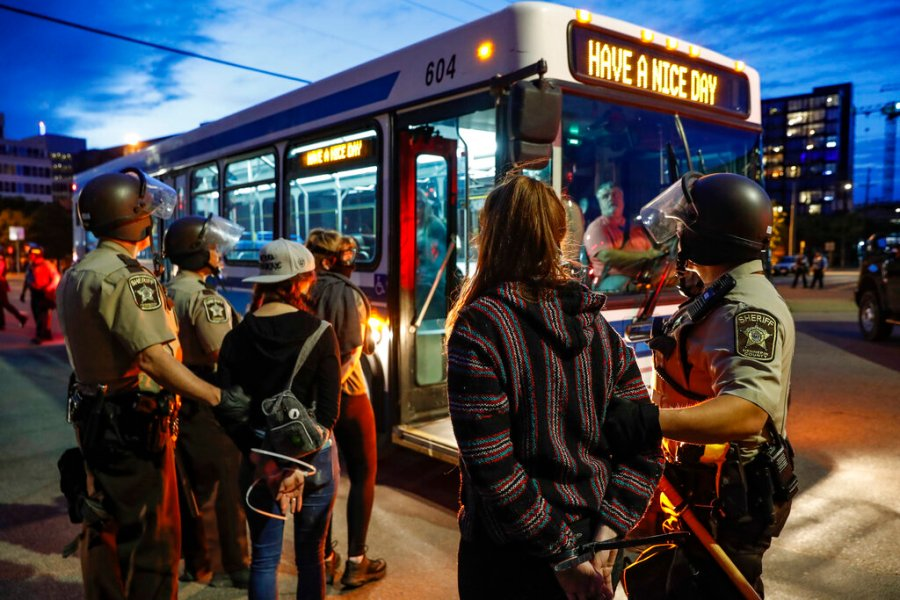 Arrested protesters are loaded onto a transport bus by police on South Washington Street in Minneapolis. (AP Photo/John Minchillo)