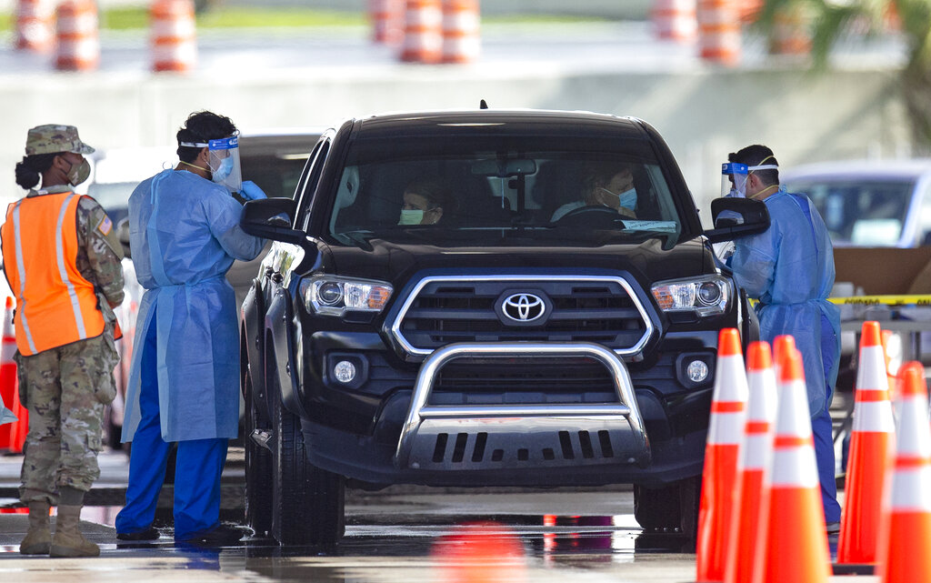 A National Guard troop directs cars as a citizens are being tested by a healthcare workers at the COVID-19 drive-thru testing center at Hard Rock Stadium in Miami Gardens as the coronavirus pandemic continues on Sunday, July 19, 2020. (David Santiago/Miami Herald via AP)