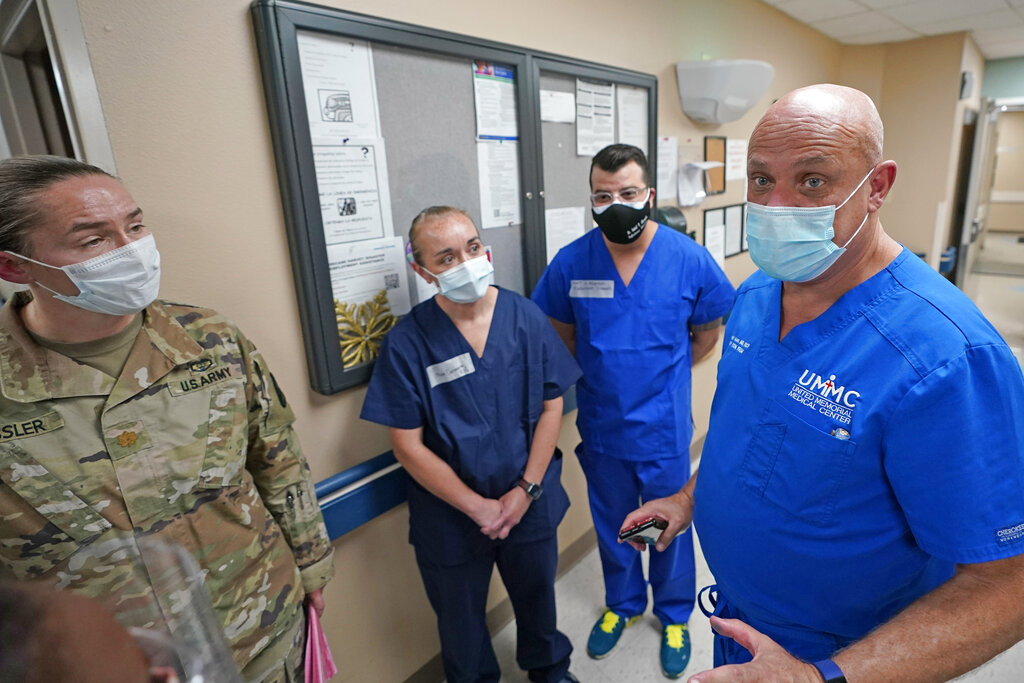 United Memorial Medical Center's Dr. Joseph Varon, right, talks with military members of the Urban Augmentation Medical Task Force in Houston. Soldiers will treat COVID-19 patients inside a wing at the hospital as Texas receives help from across the country to deal with its coronavirus surge. (AP Photo/David J. Phillip)