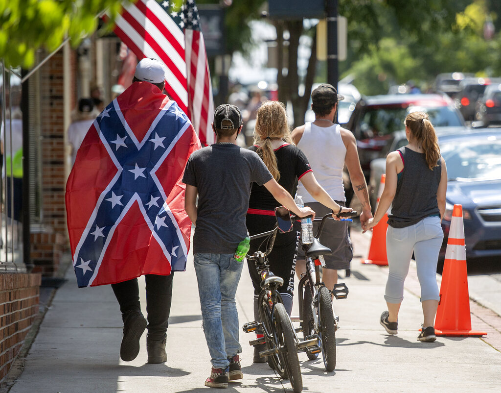 A man wears a Confederate flag while walking with others in Marion, Va. (Andre Teague/Bristol Herald Courier via AP, File)