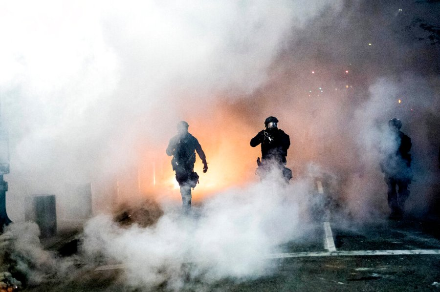 Federal officers use crowd control munitions to disperse protesters on Tuesda in Portland, Ore. (AP Photo/Noah Berger)