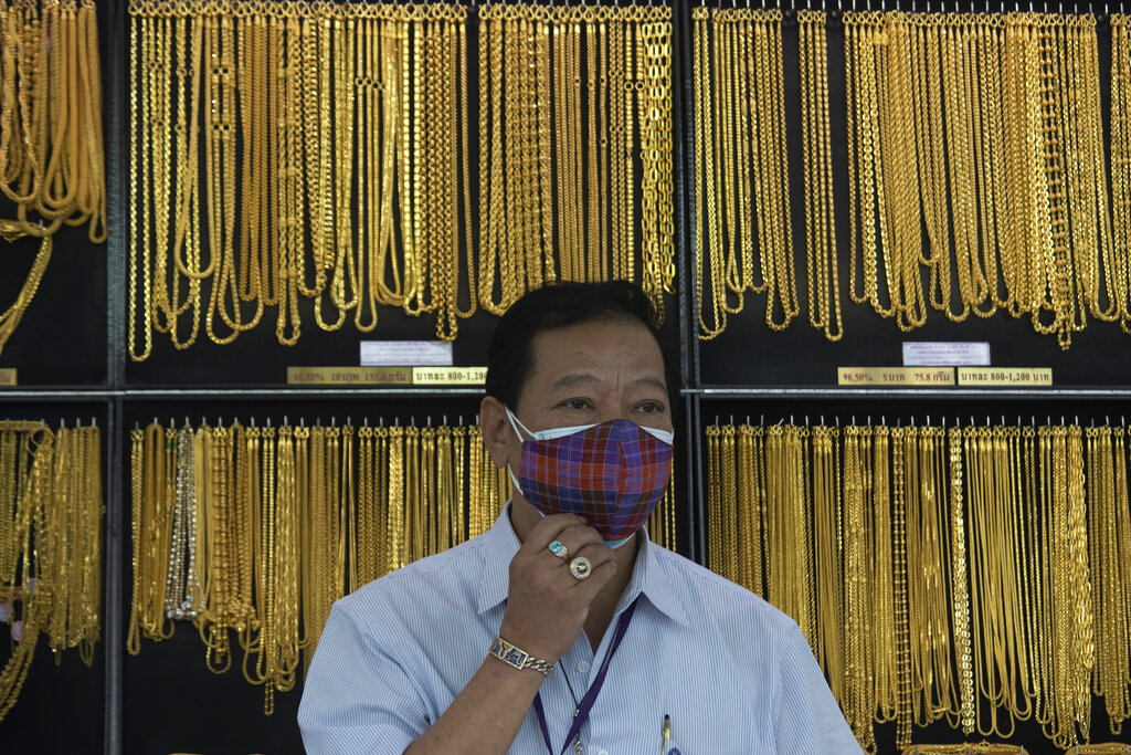 A Thai shopkeeper adjusts his face mask at a gold shop in Bangkok, Thailand. The price of gold surged more than $30 on Monday to over $1,926 per ounce as investors step up buying of the precious metal often sought in times of uncertainty. (AP Photo/Sakchai Lalit, Fil