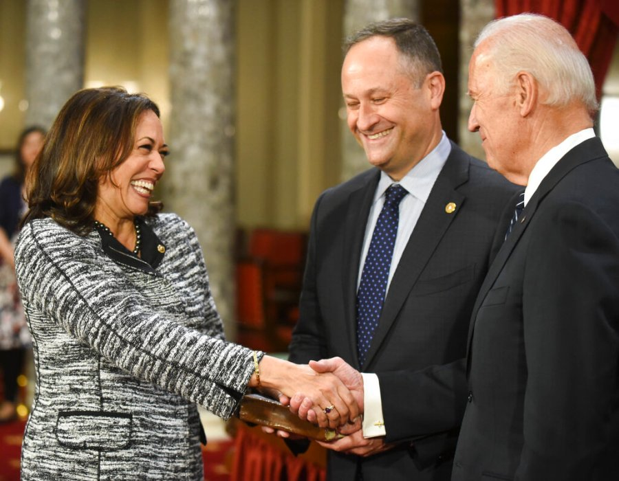 Then-Vice President Joe Biden, right, shakes hands with Sen. Kamala Harris as her husband Douglas Emhoff watches during a a mock swearing in ceremony in the Old Senate Chamber on Capitol Hill in Washington in 2017. (AP Photo/Kevin Wolf, File)