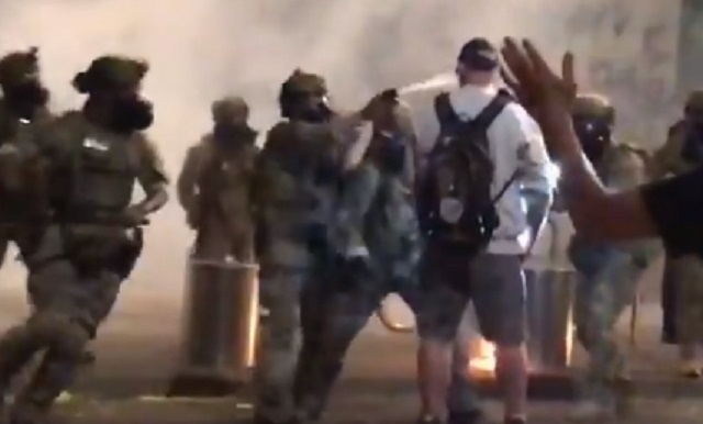 A Navy veteran named Chris David (backpack sweatshirt) is beaten and peppers-sprayed by federal officers in downtown Portland, July 18, 2020 (Screen grabs from tweet by Zane Sparling of the Portland Tribune)