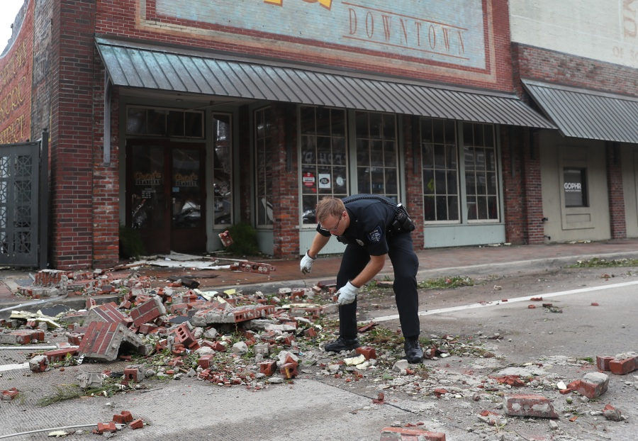 A Lake Charles police officer helps clear the streets in the downtown area after Hurricane Laura. (Photo by Joe Raedle/Getty Images)