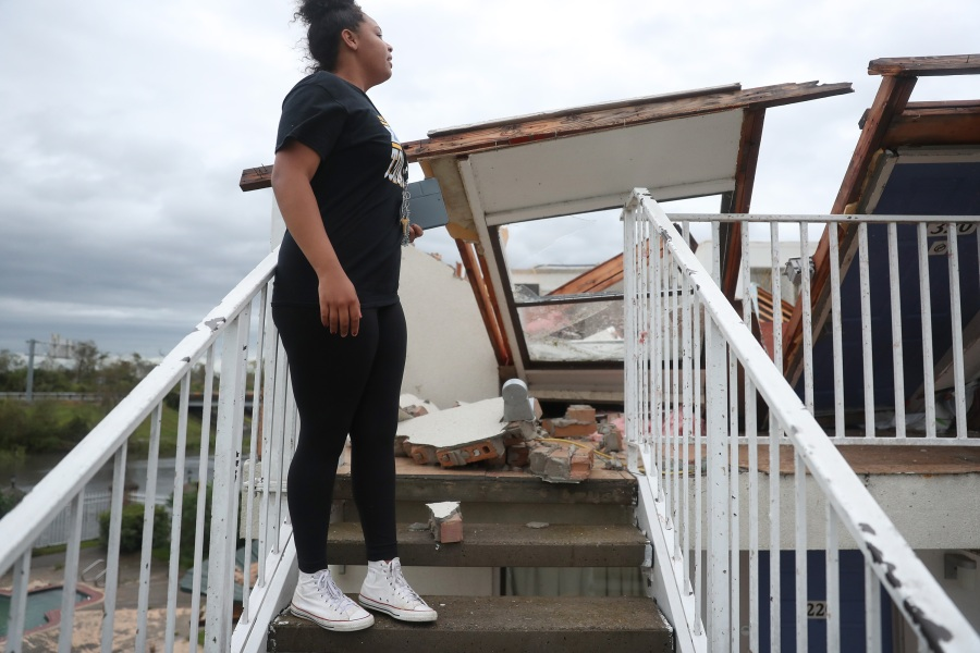 Kyana Myers looks into a room that had its roof blown off as Hurricane Laura passed through Lake Charles, Louisiana.(Photo by Joe Raedle/Getty Images)