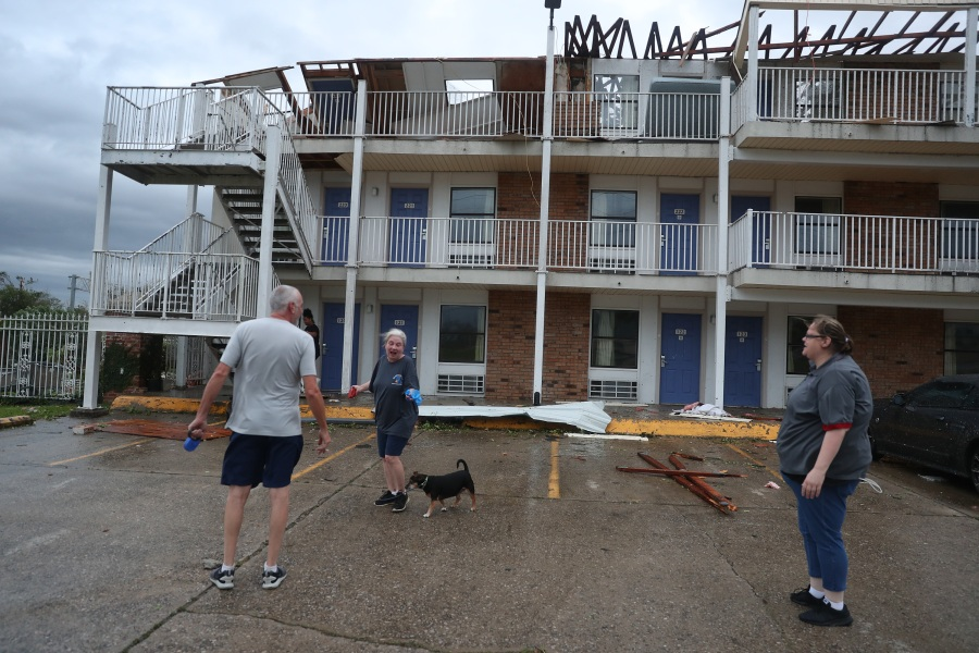 People stand next to a hotel that had parts of its roof blown off as Hurricane Laura passed through Lake Charles, Louisiana. The hurricane hit with powerful winds causing extensive damage to the city. (Photo by Joe Raedle/Getty Images)