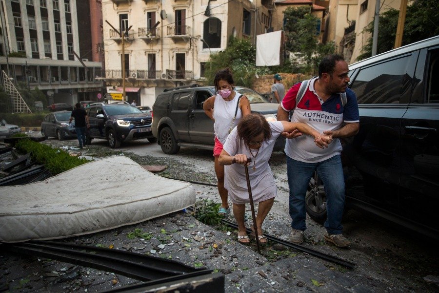 An elderly woman is helped while walking through debris after a large explosion on Aug. 4, 2020 in Beirut, Lebanon.
