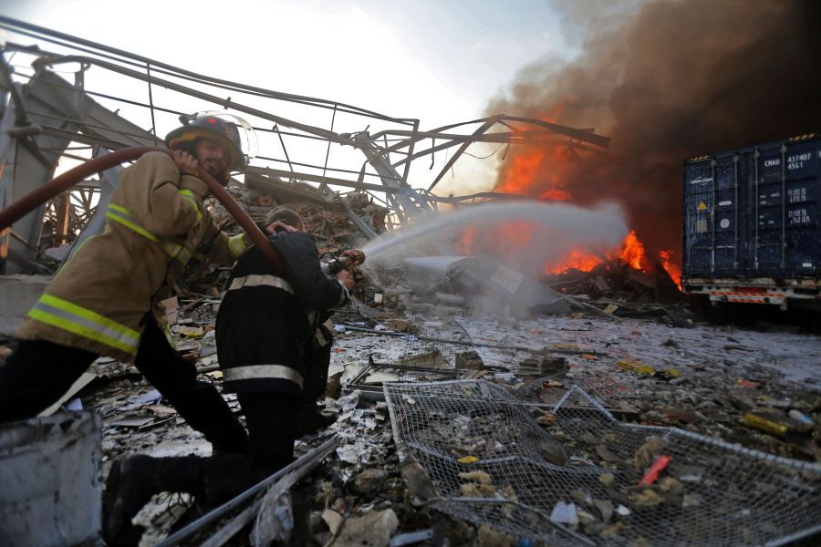Lebanese firefights extinguish fire at the scene of an explosion at the port in the capital Beirut.