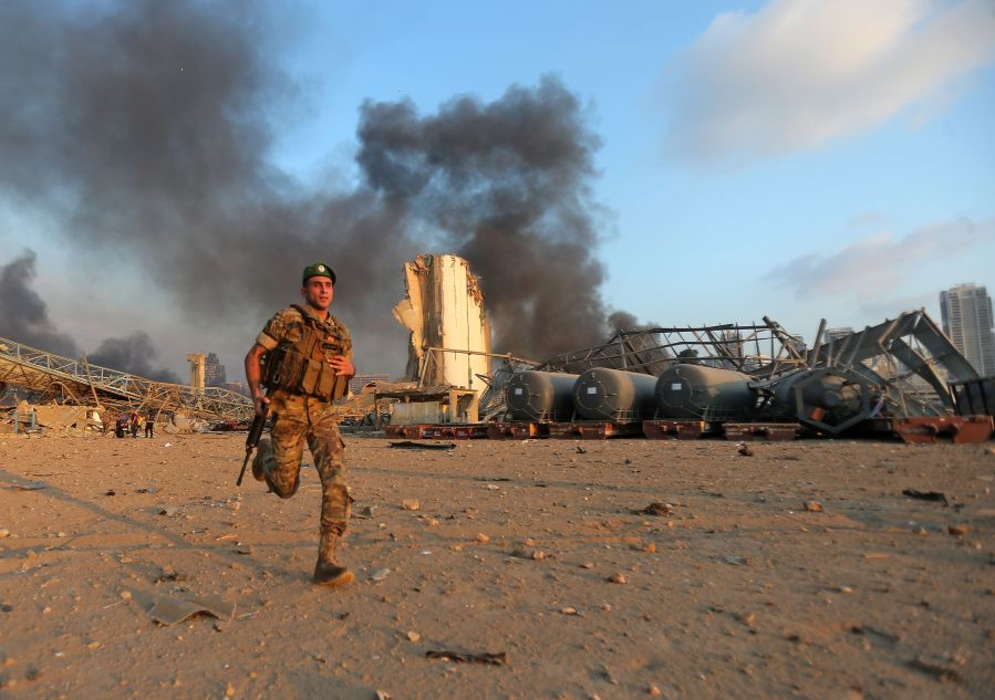 A Lebanese army soldier runs at the scene of an explosion at the port of Lebanon's capital Beirut.
