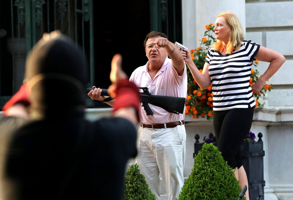 Armed homeowners Mark and Patricia McCloskey stand in front their house in St. Louis confronting protesters. (Laurie Skrivan/St. Louis Post-Dispatch via AP File)