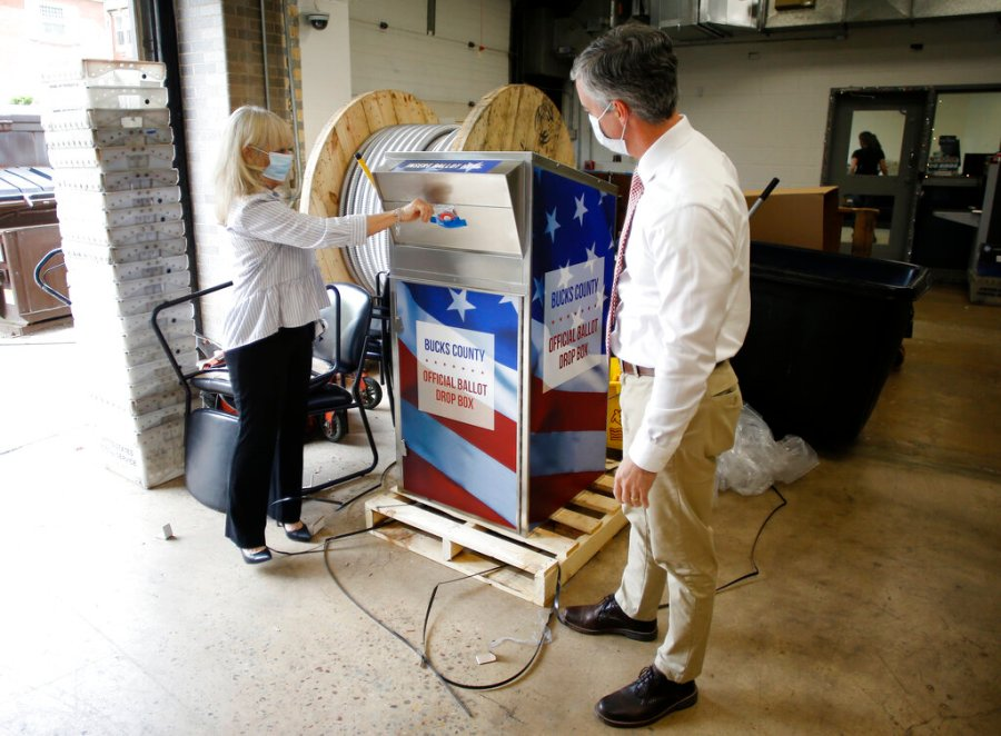Bucks County commissioners Diane Ellis-Marseglia, left, and Robert Harvie unpack a new ballot drop box at the county's administration building prior to the primary election in Doylestown, Pa. With the Trump administration openly trying to undermine mail-in voting this fall, some election officials around the country are hoping to bypass the Postal Service by installing lots of ballot drop boxes in libraries, community centers and other public places. (AP Photo/Matt Slocum, File