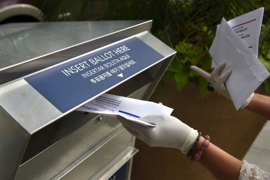 A woman wearing gloves drops off a mail-in ballot at a drop box in Hackensack, N.J. (AP Photo/Seth Wenig, File)