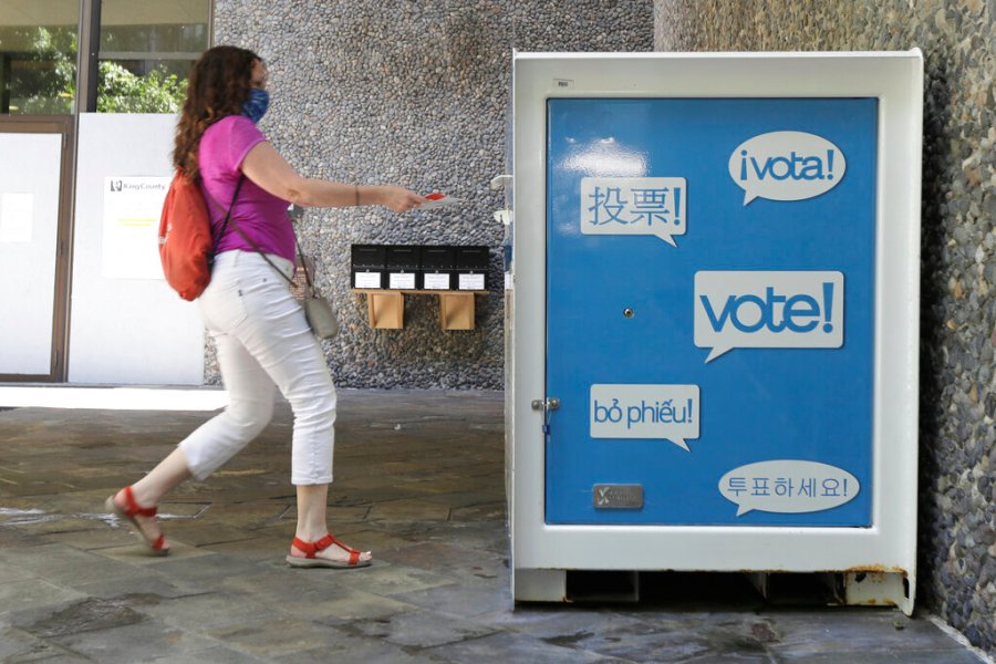 A woman drops off a ballot for Washington State's primary election at a collection box at the King County Administration Building in Seattle. (AP Photo/Ted S. Warren, File)