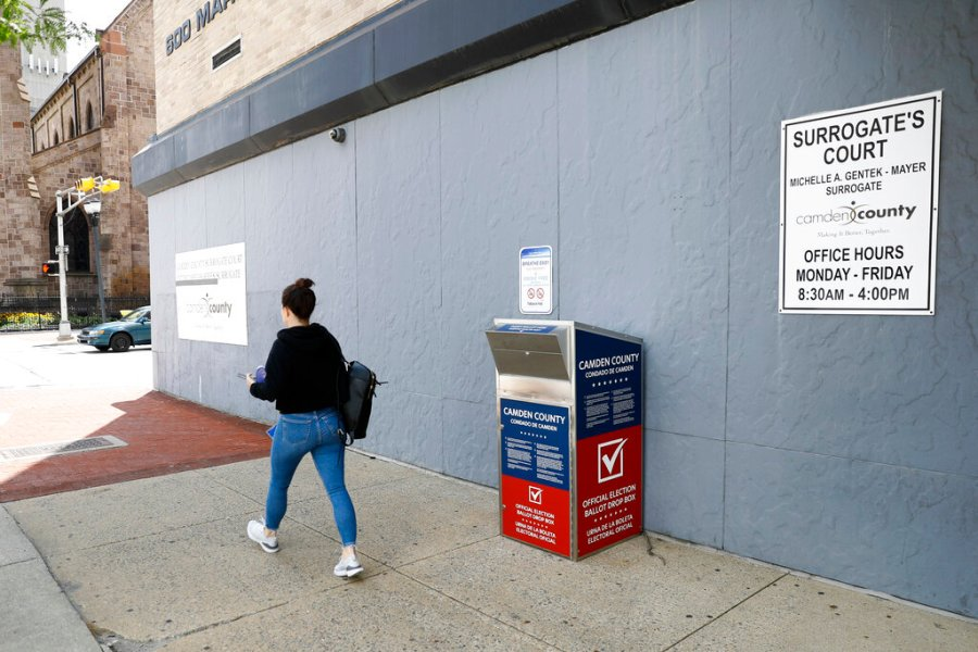 A woman walks past a vote-by-mail drop box for the New Jersey primary election outside the Camden, N.J., Administration Building. With the Trump administration openly trying to undermine mail-in voting this fall, some election officials around the country are hoping to bypass the Postal Service by installing lots of ballot drop boxes in libraries, community centers and other public places. (AP Photo/Matt Slocum, File)
