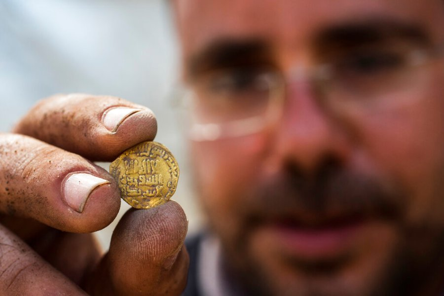 Israeli archaeologist Shahar Krispin displays a gold coin that was discovered at an archeological site in central Israel. (AP Photo/Sipa Press, Heidi Levine, Pool)