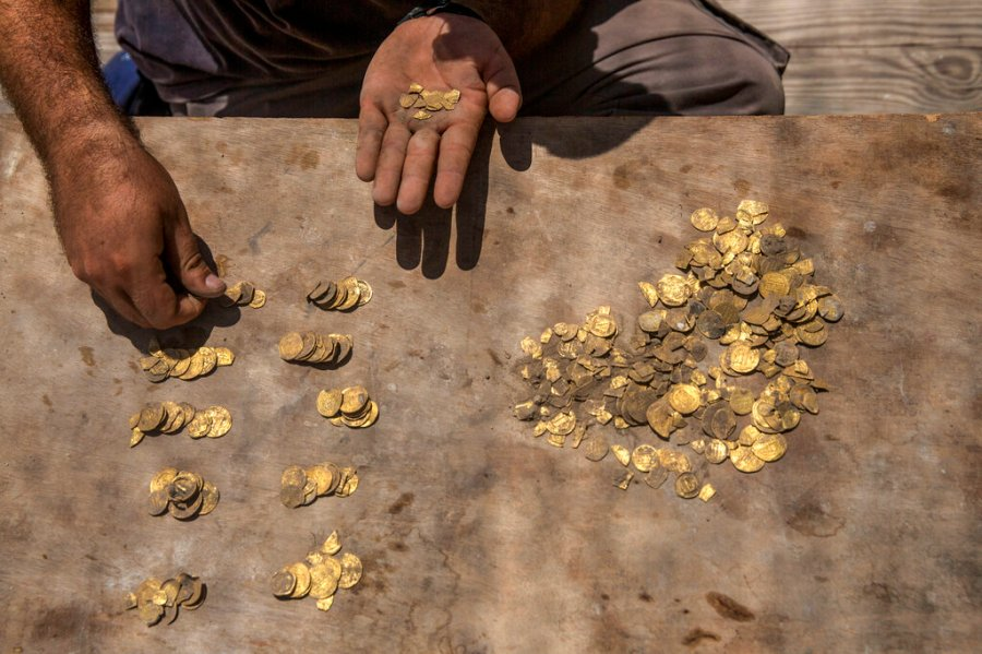 Israeli archaeologist Shahar Krispin counts gold coins buried in a pottery vessel that was discovered at an archeological site in central Israel. (AP Photo/Sipa Press, Heidi Levine, Pool)