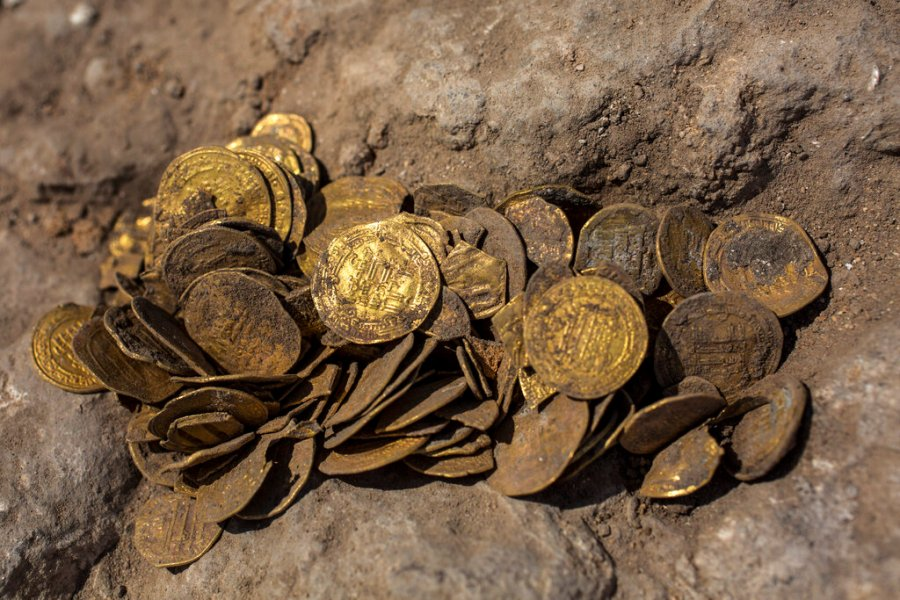 "A hoard of gold coins that was discovered at an archeological site in central Israel. Israeli archaeologists have announced the discovery of a trove of early Islamic gold coins during recent salvage excavations near the central city of Yavn Tel Aviv. The collection of 425 complete gold coins, most dating to the Abbasid period around 1,100 years ago, is a ""extremely rare"" find. (AP Photo/Sipa Press, Heidi Levine, Pool)"