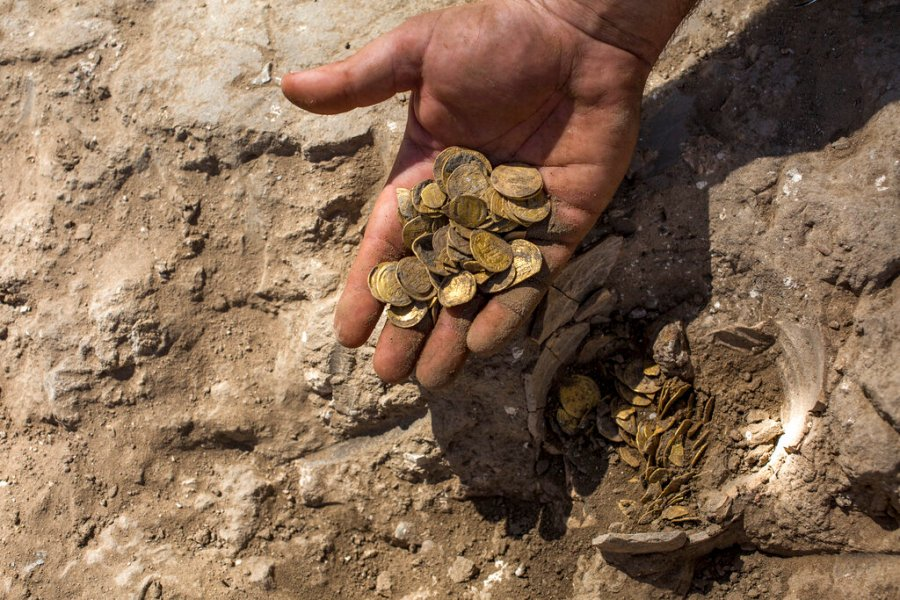 """Israeli archaeologist Shahar Krispin displays gold coins that were discovered at an archeological site in central Israel. Israeli archaeologists have announced the discovery of a trove of early Islamic gold coins during recent salvage excavations near the central city of Yavn Tel Aviv. The collection of 425 complete gold coins, most dating to the Abbasid period around 1,100 years ago, is a """"extremely rare"""" find. (AP Photo/Sipa Press, Heidi Levine, Pool)"""