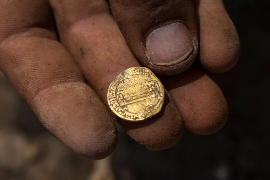"Israeli archaeologist Shahar Krispin displays a gold coin that was discovered at an archeological site in central Israel. Israeli archaeologists have announced the discovery of a trove of early Islamic gold coins during recent salvage excavations near the central city of Yavn Tel Aviv. The collection of 425 complete gold coins, most dating to the Abbasid period around 1,100 years ago, is a ""extremely rare"" find. (AP Photo/Sipa Press, Heidi Levine, Pool)"