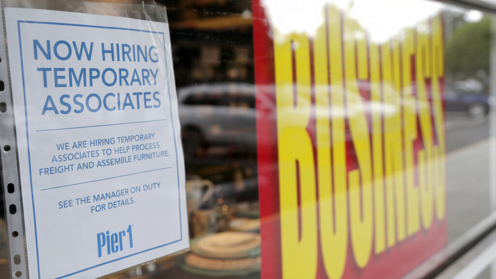 A sign advertises hiring