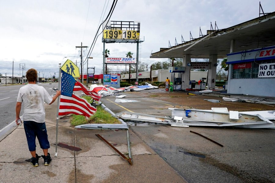 Dustin Amos walks near debris at a gas station in Lake Charles. (AP Photo/Gerald Herbert)