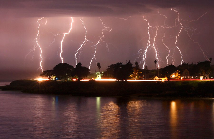 A rare lightning storm crackles over Mitchell's Cove in Santa Cruz, California around 3 a.m. Sunday morning. The severe storm system rolled through the San Francisco and Monterey Bay area early Sunday, packing a combination of dry lightning and high winds that triggered wildfires throughout the region. (Shmuel Thaler/The Santa Cruz Sentinel via AP)