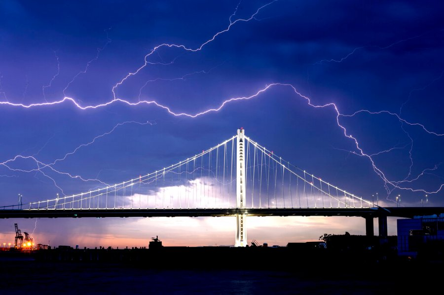 Lightning forks over the San Francisco-Oakland Bay Bridge as a storm passes over Oakland, Calif., Sunday. Numerous lightning strikes early Sunday sparked brush fires throughout the region. (AP Photo/Noah Berger)