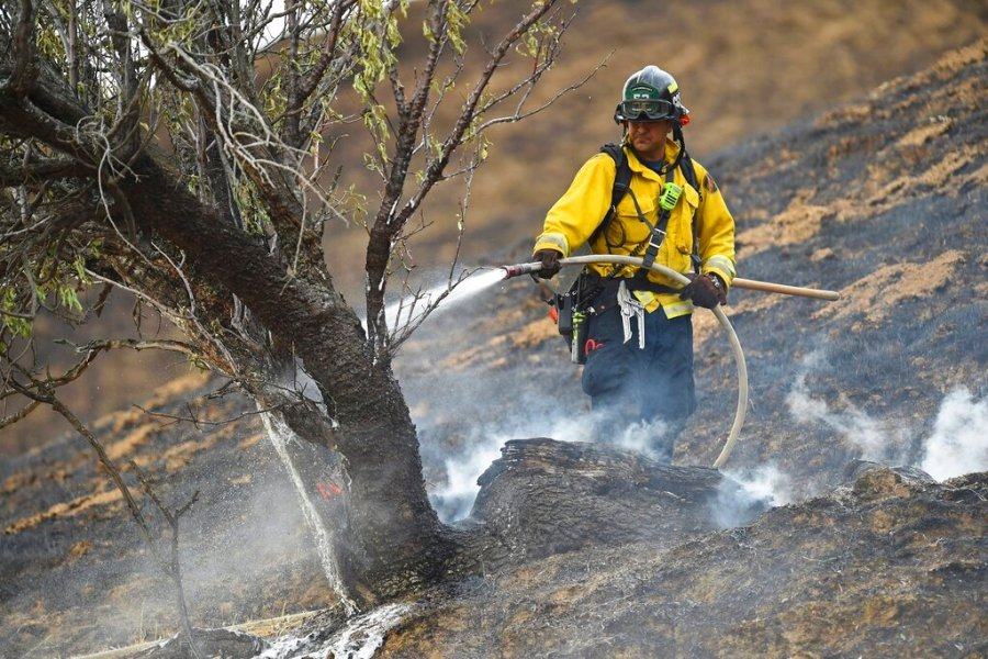 A firefighter extinguishes a hot spot from a vegetation fire caused by a lightning strike on Marsh Creek Road in Brentwood, Calif., Sunday. (Jose Carlos Fajardo/Bay Area News Group)