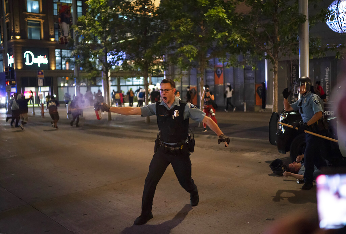 Police spray a substance to clear the area where a colleague was down at the Nicollet Mall in Minneapolis. The Minneapolis mayor imposed a curfew Wednesday night and requested National Guard help after unrest broke out downtown following what authorities said was misinformation about the death of a Black homicide suspect. (Jeff Wheeler/Star Tribune via AP)