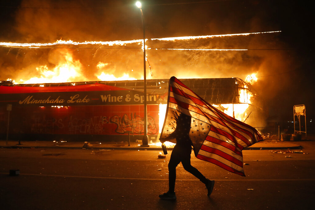 A protester carries a U.S. flag upside down, a sign of distress, next to a burning building, in Minneapolis during protests over the death of George Floyd. (AP Photo/Julio Cortez, File)