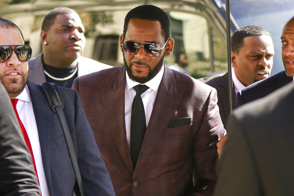 Singer R. Kelly, center, arrives at the Leighton Criminal Court building for an arraignment on sex-related felonies in Chicago in 2019. Federal prosecutors announced charges Wednesday against three men accused of threatening and intimidating women who have accused Kelly of abuse, including one man suspected of setting fire to a vehicle in Florida. (AP Photo/Amr Alfiky, File)
