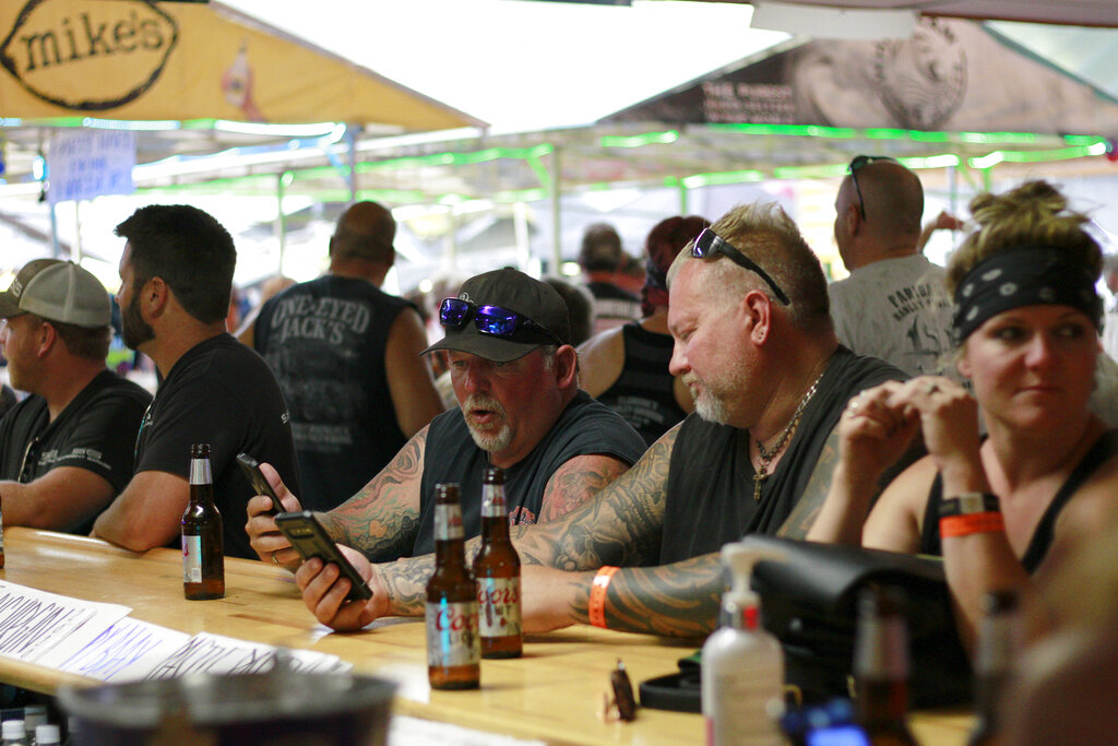 People congregate at One-Eyed Jack's Saloon during the 80th annual Sturgis Motorcycle Rally on Aug. 7th in Sturgis, South Dakota. The South Dakota Department of Health issued warnings that two people who had visited the bar may have transmitted COVID-19. (AP Photo/Stephen Groves)