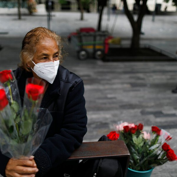"""Wearing a mask to curb the spread of the coronavirus, Martha Gonzalez Reyes, 76, sells roses outside Metro Hidalgo in central Mexico City, Monday, Aug. 10, 2020. After four months staying at home, Gonzalez returned to selling on August 1, but she says business hasn't fully rebounded. """"People have less money to spend she says, and they don't want to go out and get infected.""""(AP Photo/Rebecca Blackwell)"""