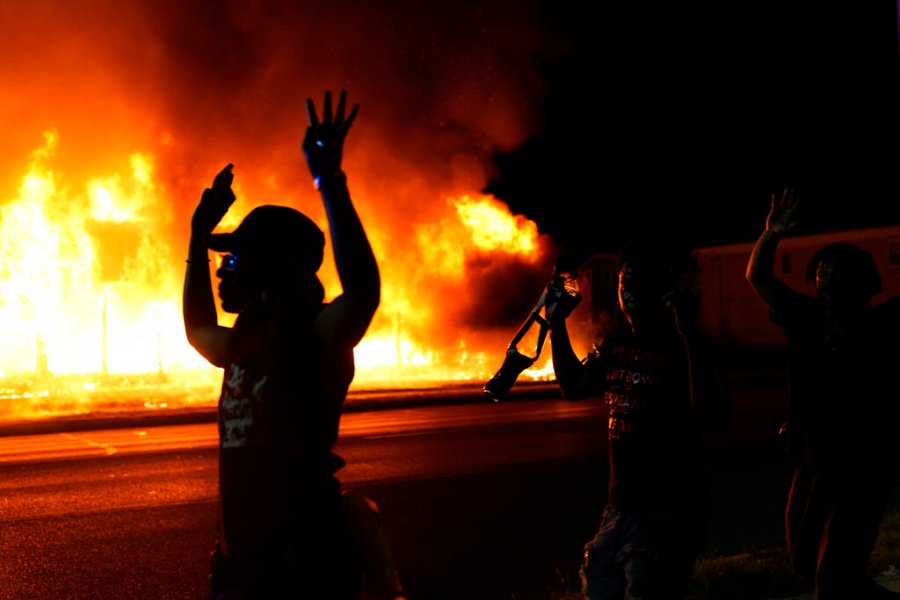 Protesters walk past police with their arms up as a building burns in the background. Protests have erupted following the police shooting of Jacob Blake a day earlier. (AP Photo/David Goldman)