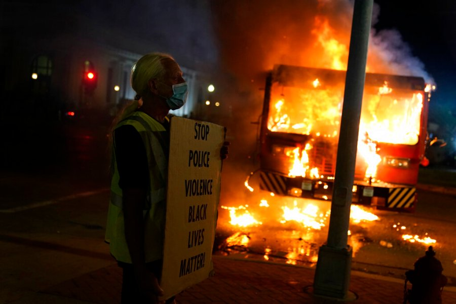 A protester stands near a burning garbage truck outside the Kenosha County Courthouse. Protesters converged on the county courthouse during a second night of clashes after the police shooting of Jacob Blake a day earlier turned Kenosha into the nation's latest flashpoint city in a summer of racial unrest. (AP Photo/David Goldman)