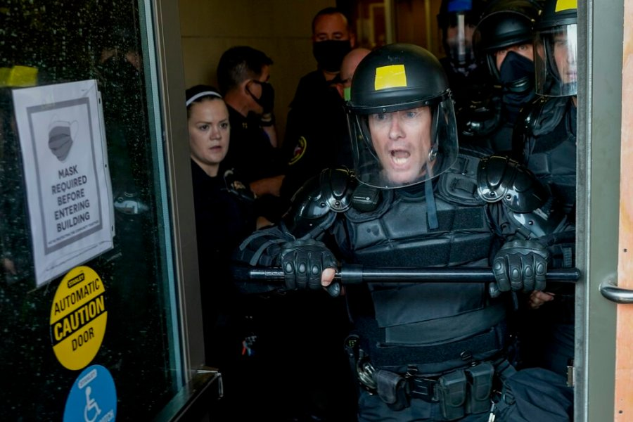 Police try to secure the public safety building from protesters in Kenosha, Wis. (AP Photo/Morry Gash)