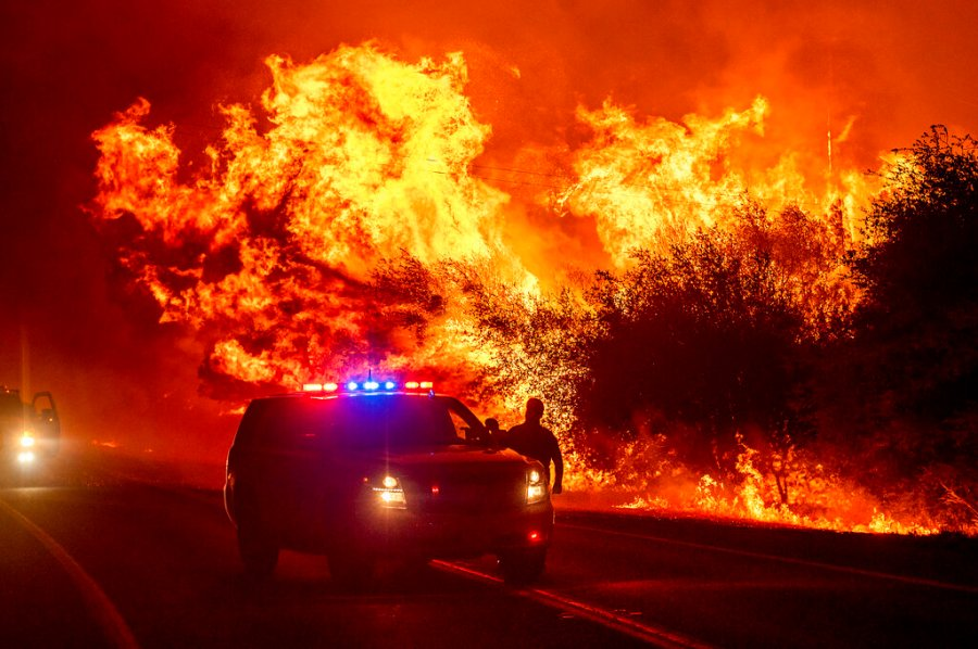 Flames lick above vehicles on Highway 162 as the Bear Fire burns in Oroville, Calif., on Wednesday. The blaze, part of the lightning-sparked North Complex, expanded at a critical rate of spread as winds buffeted the region. (AP Photo/Noah Berger)