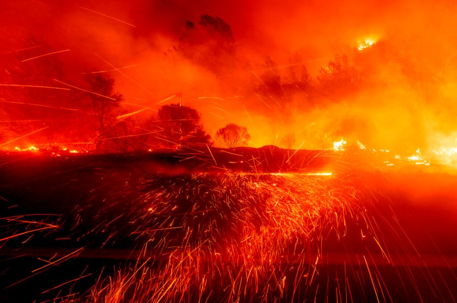 Embers fly across a roadway as the Bear Fire burns in Oroville, Calif., on Wednesday. The blaze, part of the lightning-sparked North Complex, expanded at a critical rate of spread as winds buffeted the region. (AP Photo/Noah Berger)
