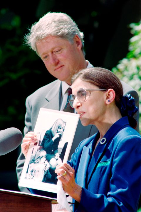 US Supreme Court nominee Ruth Bader Ginsburg (R) holds a picture of her granddaughter with First Lady Hillary Clinton in a New York school as President Bill Clinton looks on at the White House in 1993. (PAUL J. RICHARDS/AFP via Getty Images)