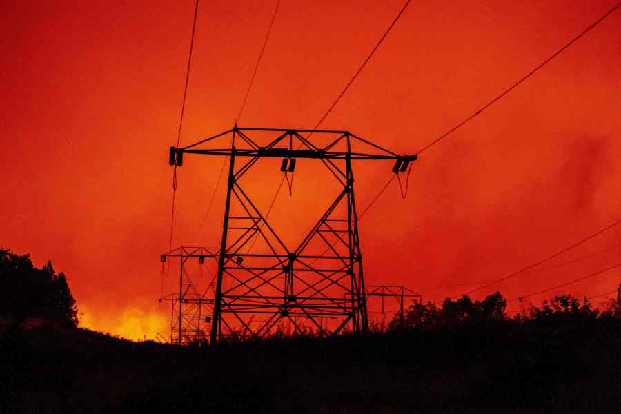 High-tension power lines are seen against a burning landscape in the Tollhouse area of unincorporated Fresno County, California.(Photo by JOSH EDELSON/AFP via Getty Images)