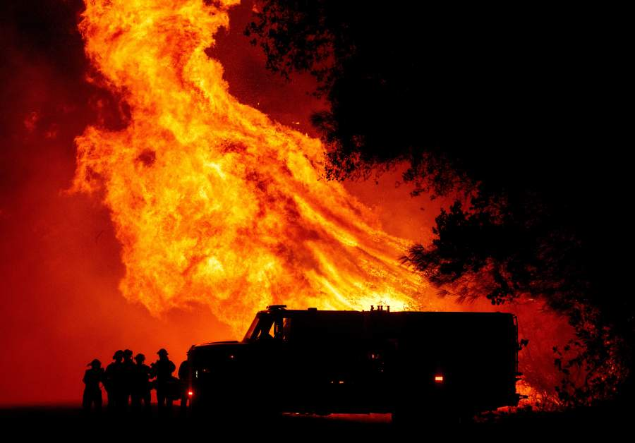 Butte county firefighters watch as flames tower over their truck at the Bear fire in Oroville, California.  (Photo by JOSH EDELSON/AFP via Getty Images)