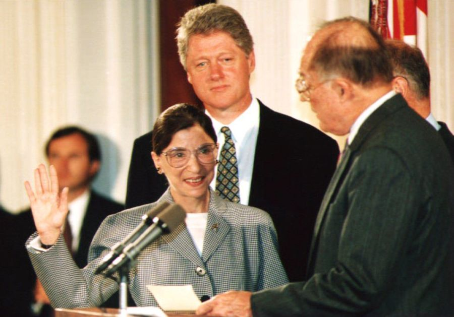 Chief Justice of the U.S. Supreme Court William Rehnquist administers the oath of office to newly-appointed U.S. Supreme Court Justice Ruth Bader Ginsburg as President Bill Clinton looks on in 1993. Ginsburg is the 107th Supreme Court justice and the second woman to serve on the high court. (Photo credit should read KORT DUCE/AFP via Getty Images)