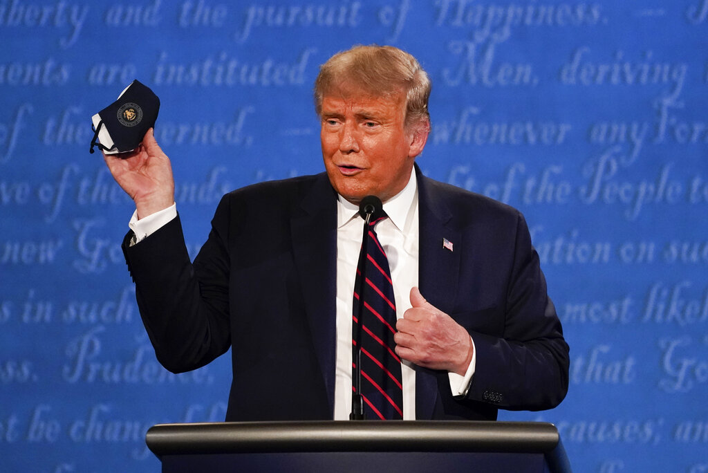 President Donald Trump holds up a face mask during the first presidential debate at Case Western University and Cleveland Clinic, in Cleveland, Ohio. (AP Photo/Julio Cortez)