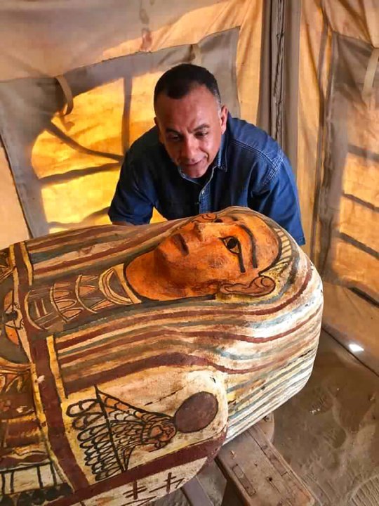Mostafa Waziri, Egypt's secretary general of the Supreme Council of Antiquities, poses with one of more than two dozen ancient coffins unearthed near the famed Step Pyramid of Djoser in Saqqara, south of Cairo, Egypt. (Ministry of Tourism and Antiquities via AP)