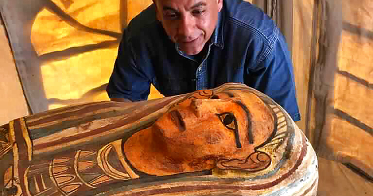 Mostafa Waziri, secretary general of Egypt's Supreme Council of Antiquities, poses with one of more than two dozen ancient coffins unearthed near the famed Step Pyramid of Djoser in Saqqara, south of Cairo, Egypt. (Ministry of Tourism and Antiquities via AP)