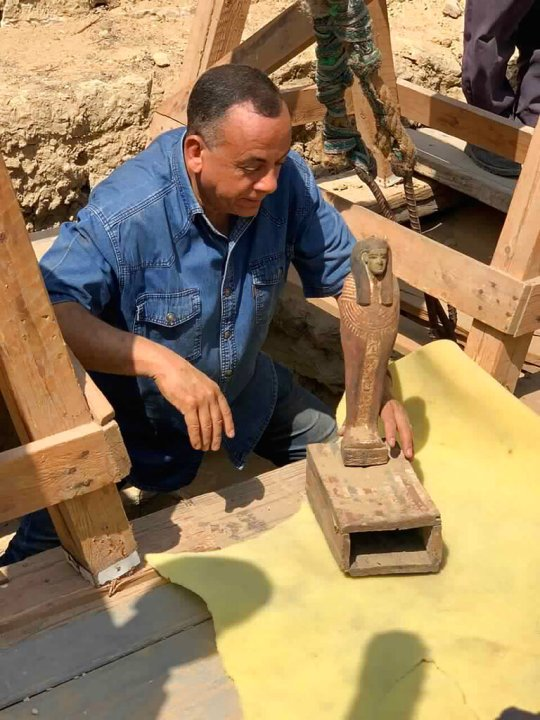 Mostafa Waziri, secretary general of Egypt's Supreme Council of Antiquities, displays an artifact found along with more than two dozen ancient coffins unearthed near the famed Step Pyramid of Djoser in Saqqara, south of Cairo, Egypt. (Ministry of Tourism and Antiquities via AP)