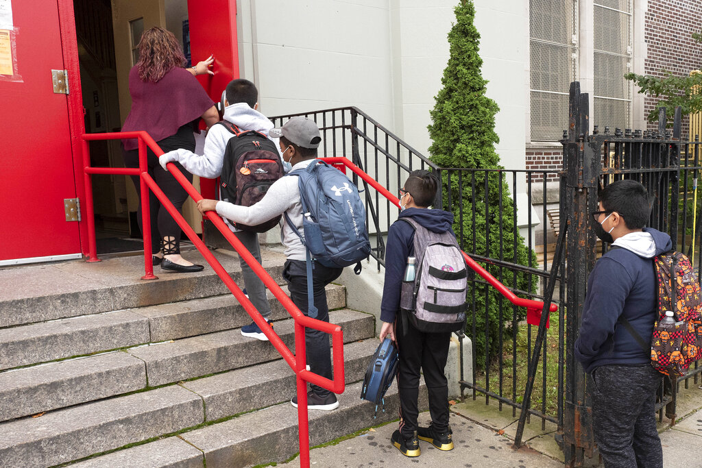 A teacher leads her students into an elementary school in the Brooklyn borough of New York on Tuesday. The coronavirus is infecting a rising number of American children and teens in a trend authorities say appears driven by school reopenings and the resumption of sports, playdates and other activities. (AP Photo/Mark Lennihan)