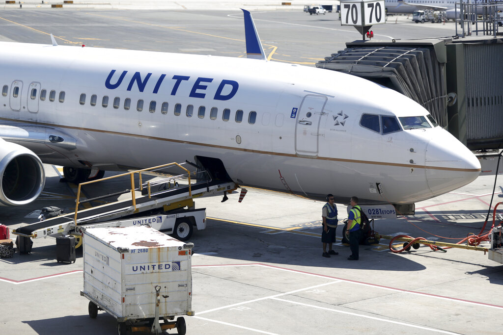 A United Airlines commercial jet sits at a gate at Terminal C of Newark Liberty International Airport in 2018. United plans to furlough about 16,000 employees in October 2020 as air travel continues to be hammered by the pandemic. That's fewer furloughs than United predicted in July, when it warned 36,000 employees that they could lose their jobs. (AP Photo/Julio Cortez, File)